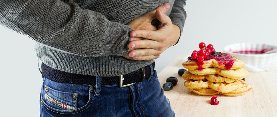 Digestive signs of celiac with man holding stomach ache.